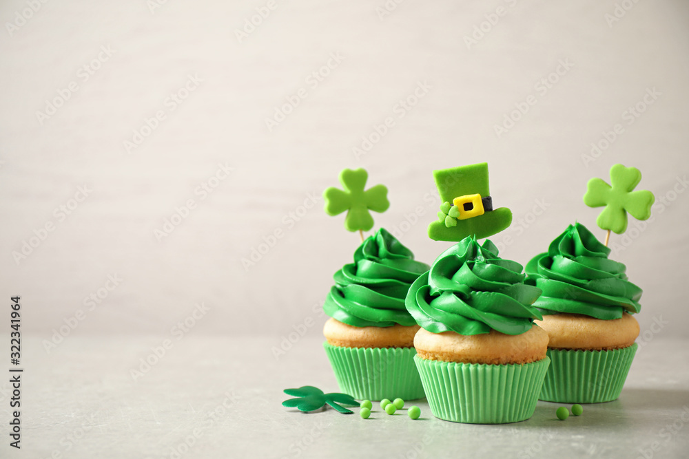 Fototapeta Delicious decorated cupcakes on light table, space for text. St. Patrick's Day celebration
