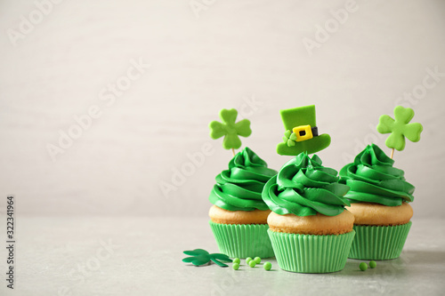 Fototapeta Delicious decorated cupcakes on light table, space for text. St. Patrick's Day celebration obraz