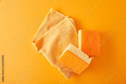 top view of rag and yellow sponges for house cleaning on orange