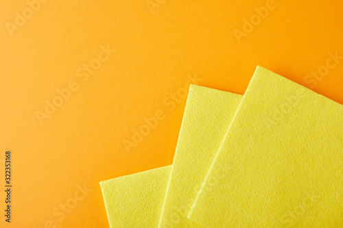 top view of yellow rags for house cleaning on orange with copy space