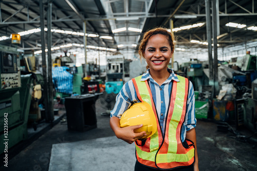 Obraz attractive young african woman smiling and working engineering in industry.Portrait of young female worker in the factory.Work at the Heavy Industry Manufacturing Facility concept. - fototapety do salonu