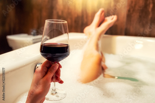 Relaxing in bathtub with glass of red wine - 322358577