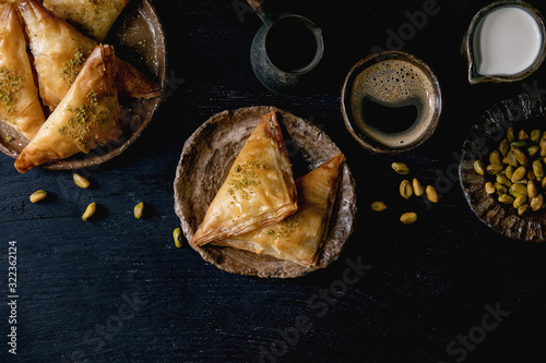 Homemade Turkish traditional dessert baklava with pistachio served on ceramic plate with bowl of nuts, cup of coffee, cream, cezva over black wooden background Canvas Print