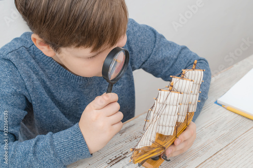 Photo A beautiful boy of 10 years old, a student of the 3rd class, studies the structure of a wooden model of a handmade ship through a magnifying glass