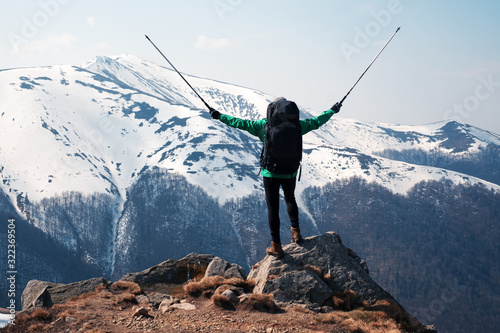 Fototapeta Amazing view with snowy mountains range and hiker with backpack on a foreground. Landscape photography obraz