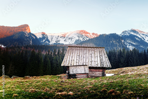 Fototapeta Old wooden hut and sunset sky in spring High Tatras mountains in Kalatowki meadow, Zakopane, Poland. Landscape photography obraz