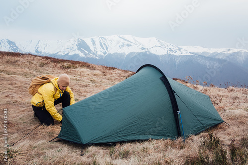 Fototapeta Tourist pitch a tent in spring mountains. Amazing highland. Landscape photography obraz
