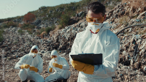 Fotografia, Obraz Portrait of male ecologist observing landfill site and writing notes