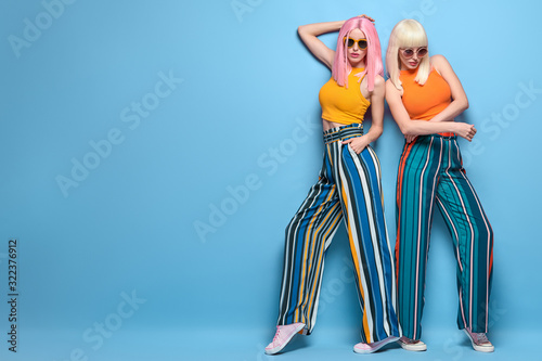 Fototapeta Fashion. Two beautiful woman, stylish clothes, trendy hair, make up. Well dressed fashionable model girl, friends on blue. Shapely gorgeous lady, blonde pink hairstyle, beauty fashion banner obraz