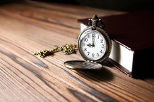 A Pocket Watch With Book Backg...
