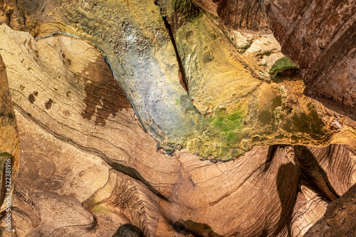 View inside the ancient cave with stone walls with additional lighting. Texture of a stone wall in a cave.