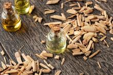A Bottle Of Cedar Essential Oil With Pieces Of Cedar Wood
