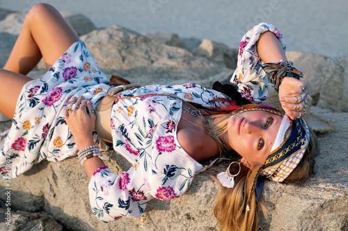 Beautiful woman wearing long dress and accessories boho style. Bohemian style girl on the beach