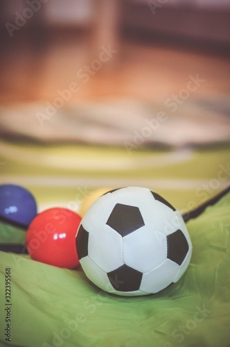 Selective focus shot of a soft toy soccer ball with plastic balls behind it.