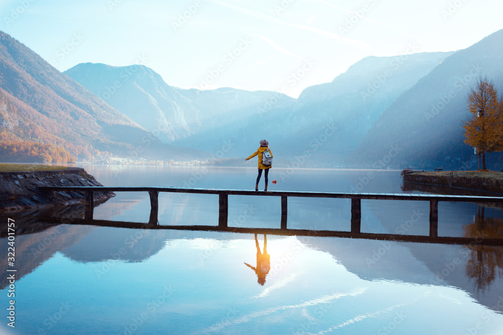 tourist girl in a hat and with a backpack sitting on a wooden bridge
