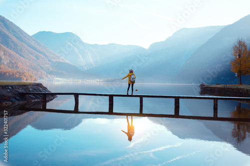 Fotomural tourist girl in a hat and with a backpack sitting on a wooden bridge