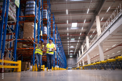 Fototapeta Shot of two workers walking through large warehouse center, observing racks with goods and planing distribution to the market. Storehouse department organization. obraz