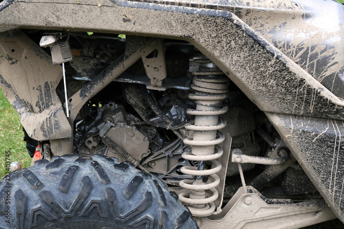 Photo Closeup of shock absorber and rubber tyre wheel of dirty ATV.