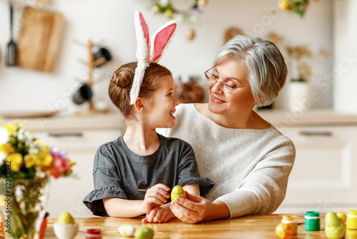 Fototapeta Happy easter! family grandmother and child with ears hare getting ready for holiday. obraz