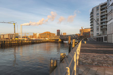 Germany, Hamburg, HafenCity Harbor At Dawn With Smoke Coming Out Of Industrial Chimneys In Background