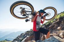 Mountain Biker Carrying His Mountain Bike