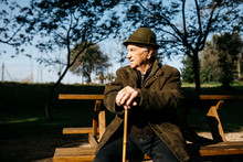 Old Man With Cane Sitting On B...