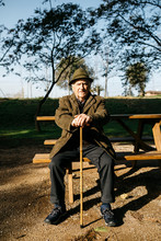 Old Man With Cane Sitting On Bench In A Park