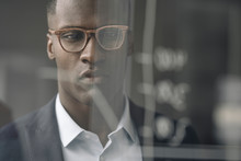 Portrait Of Young Businessman Looking At Diagram On Glass Pane
