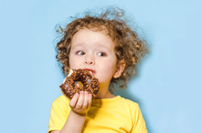 Little Curly Girl Eats, Bites A Delicious Chocolate Donut With An Appetite And With Pleasure, On Blue Background. Trend. Human Emotions In Food