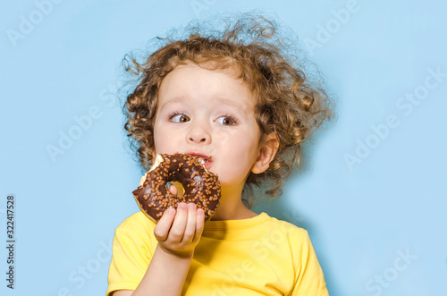 Fotografia little curly girl eats, bites a delicious chocolate donut with an appetite and with pleasure, on blue background