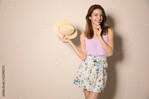 Obraz na plátně Young woman wearing floral print skirt with straw hat on beige background