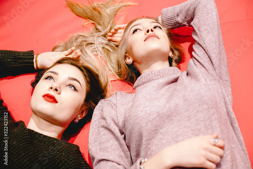 Two thoughtful emotionless young women lying on pink sofa Slika na platnu