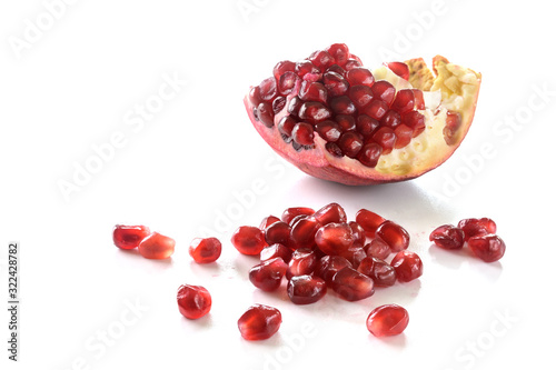 Piece of a pomegranate fruit with red juicy seeds isolated with shadows on a white background, copy space