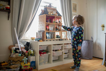 Boy In Pajamas Playing With Doll House In Bedroom