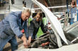 Mechanic teaching apprentice in automobile workshop