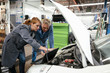 Female mechanic using laptop with colleague in repair garage