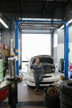 Female Mechanic Sitting On Car...