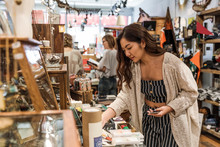 Young Woman Looking At Merchandise In Gift Shop With Smart Phone