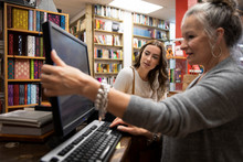 Book Store Owner Showing Computer Screen To Customer
