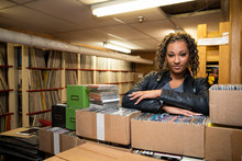 Portrait Of Confident Woman Leaning On Boxes Of CDs In Independent Record Store
