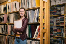 Portrait Of Cheerful Woman Holding Record In Independent Record Store