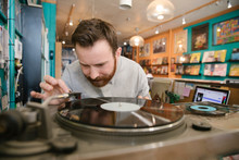Man Playing Record On Turntable In Independent Record Store