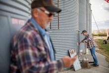 Farmers Working At Silos On Farm