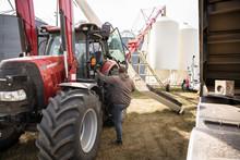 Male Farmer Climbing Up Into Tractor On Farm