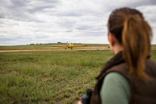 Female Farmer Watching Crop Sprayer Over Rural Field