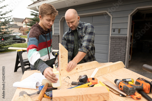 Father and son doing wood work in front of garage - 322433933