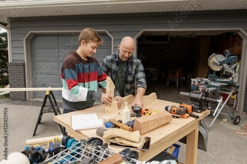 Father and son doing wood work in front of garage - 322433956