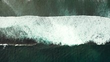 Aerial Of A Small White Wave Breaking And Crashing In The Middle Of The Dark Blue Ocean
