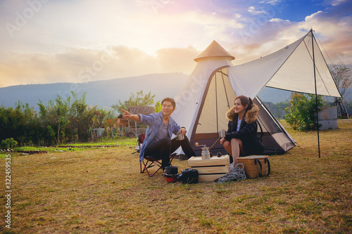 Fototapeta Young couples have good time morning on camping trip with sunrise background