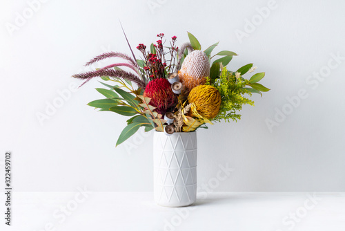 Tablou Canvas Beautiful floral arrangement of mostly Australian native banksias, eucalyptus leaves and gum nuts, fountain grass and dried kangaroo grass, in a white vase on a white table with a white background